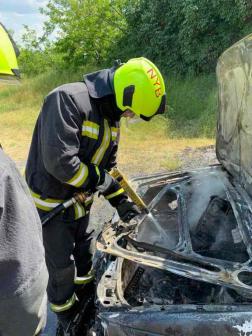 Egy nyírbátori tűzoltó a motorháztetőnél oltja a még parázsló részeket