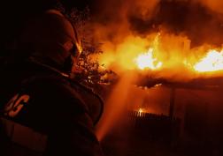 Lángoló tetőszerkezet, a fotó előterében egy tűzoltó.